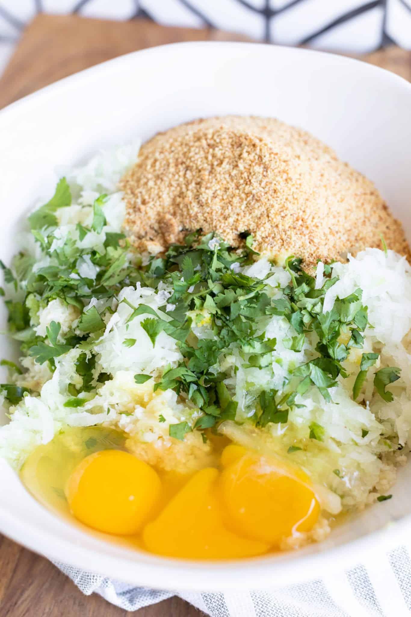 cauliflower, onion, jalapeño, garlic, egg, breadcrumb, flour, sea salt flakes and fresh parsley for crispy cauliflower hash browns all ready to mix