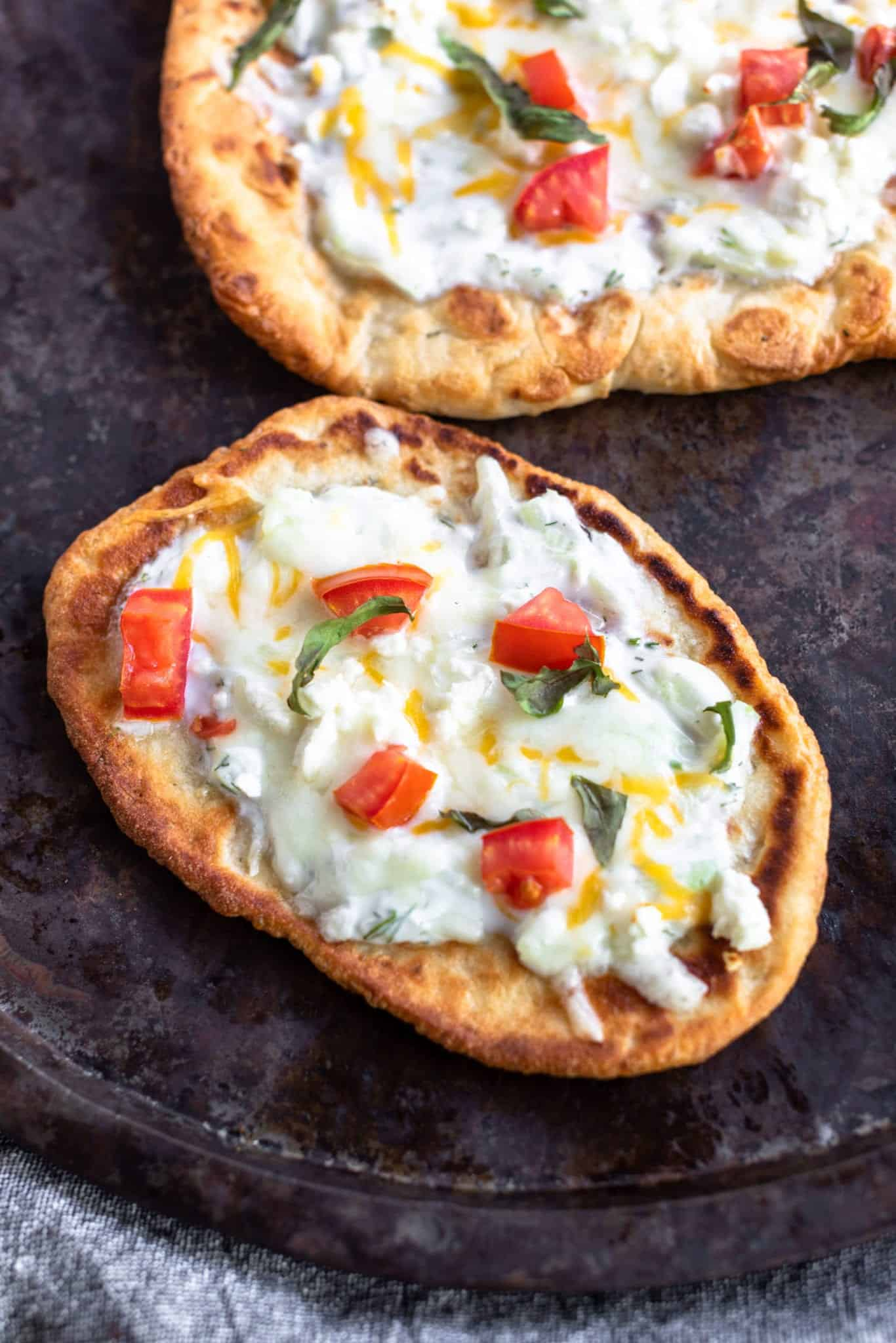 2 Mediterranean Flatbreads with tomato fresh basil and tzatziki on a golden piece of naan