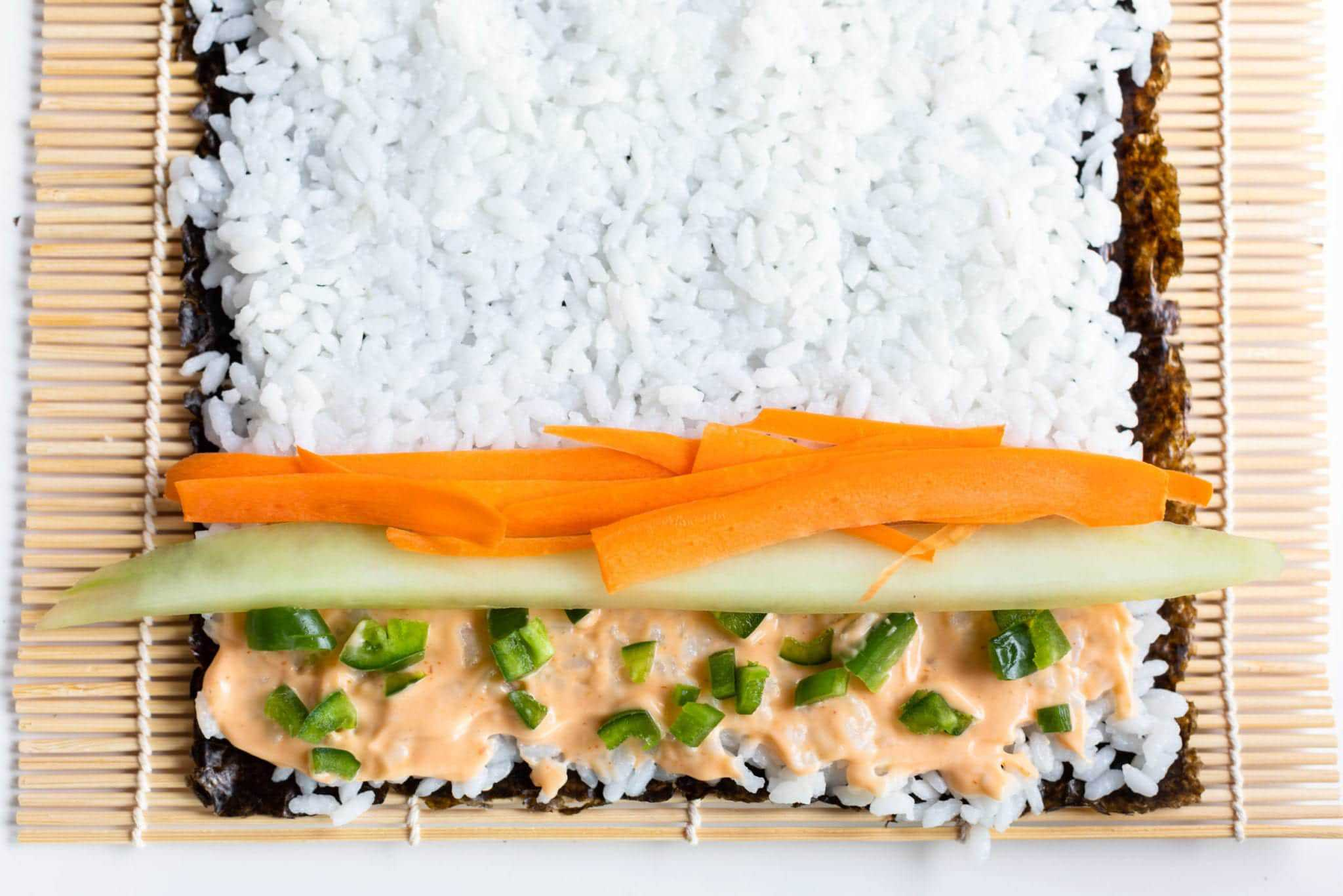 step by step sushi roll bamboo mat, nori, rice with Garlic Sriracha Ailoli, diced jalapeno, cucumber and carrots #sushi #spicytunamaki #sushirecipe #spicytuna #sushirollrecipes #spicytunamaki #crunchyspicytunaroll