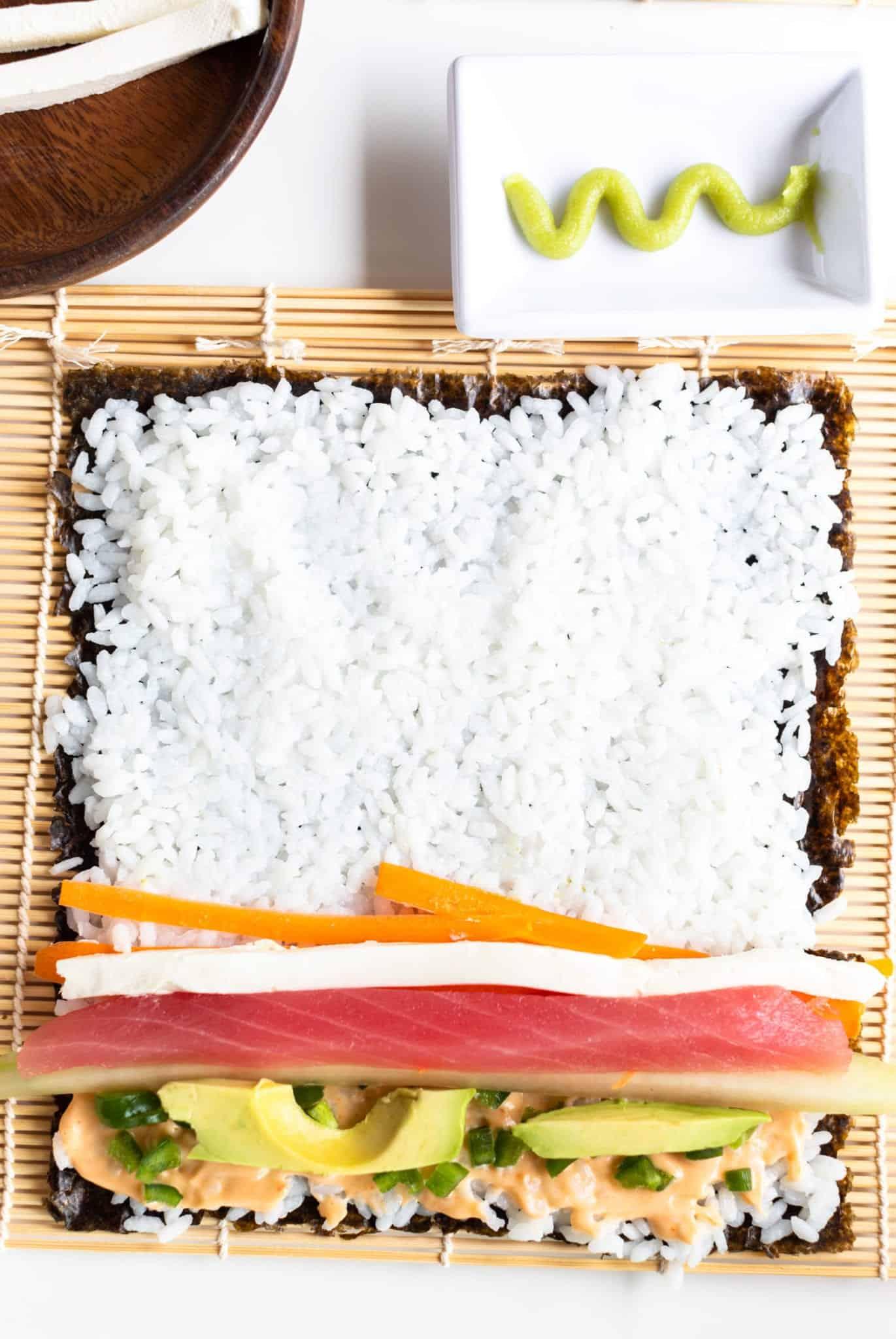 step by step sushi roll bamboo mat, nori, rice with Garlic Sriracha Ailoli, diced jalapeno, cucumber Ahi tuna, cream cheese, avocado and carrots #sushi #spicytunamaki #sushirecipe #spicytuna #sushirollrecipes #spicytunamaki #crunchyspicytunaroll