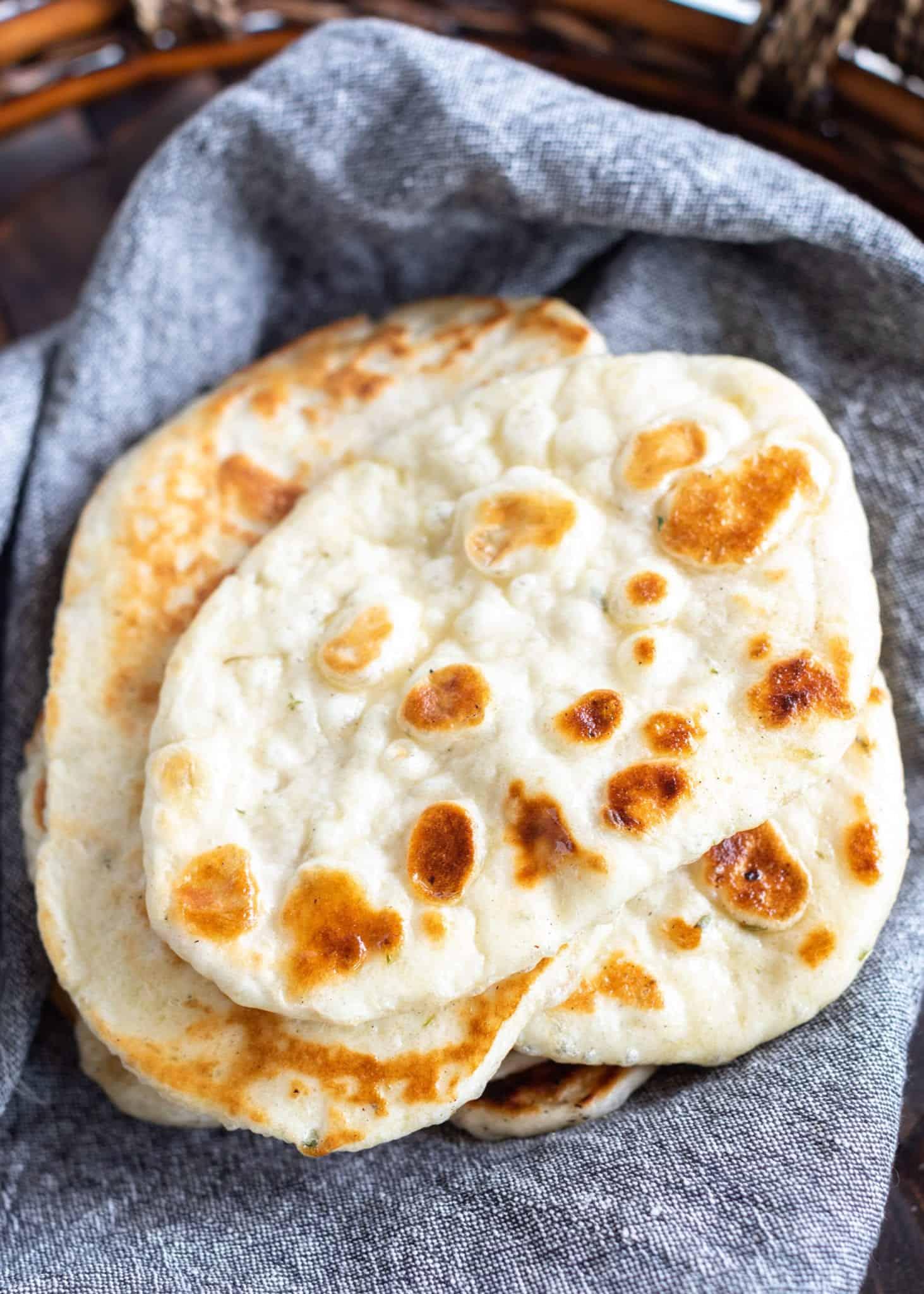 Warm Soft Garlic Herb Naan Bread stacked in denim napkin