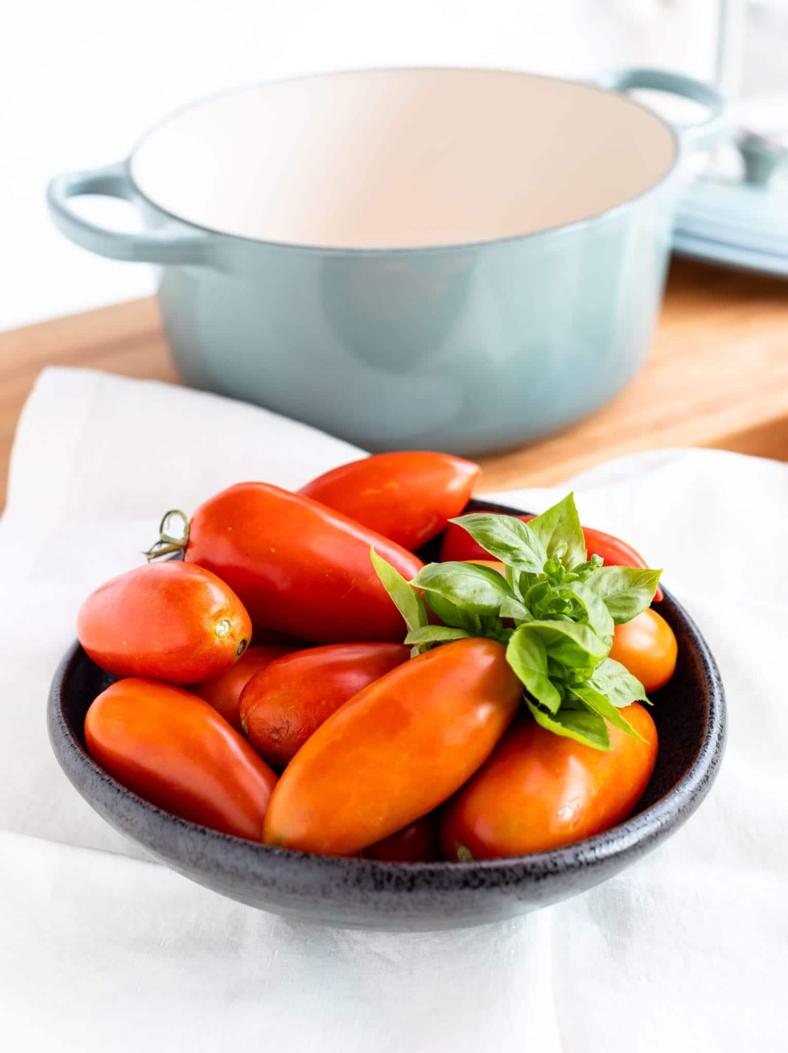 Homemade Tomato Sauce with Fresh Tomatoes - Plum tomatoes stacked in full black textured bowl with a sprig of basil on linen