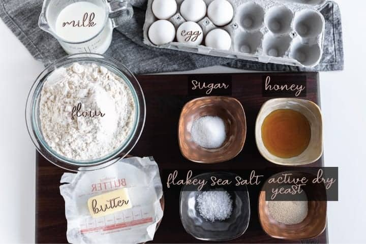 overhead shot of ingredients for rolls milk egg flour butter flakey sea salt active dry yeast honey on a walnut cutting board.