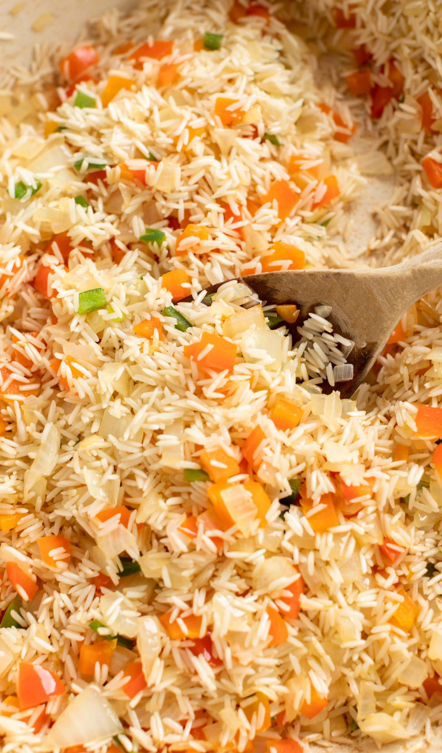 up close picture of toasted rice pilaf with red pepper jalapeno and onion before water is added to make the Everything but the Elote Chicken & Rice