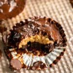 Peanut Butter Brownie Cup up close in a cupcake liner with gooey melted chocolate and 1 bite missing so you can see peanut butter brownie layers.
