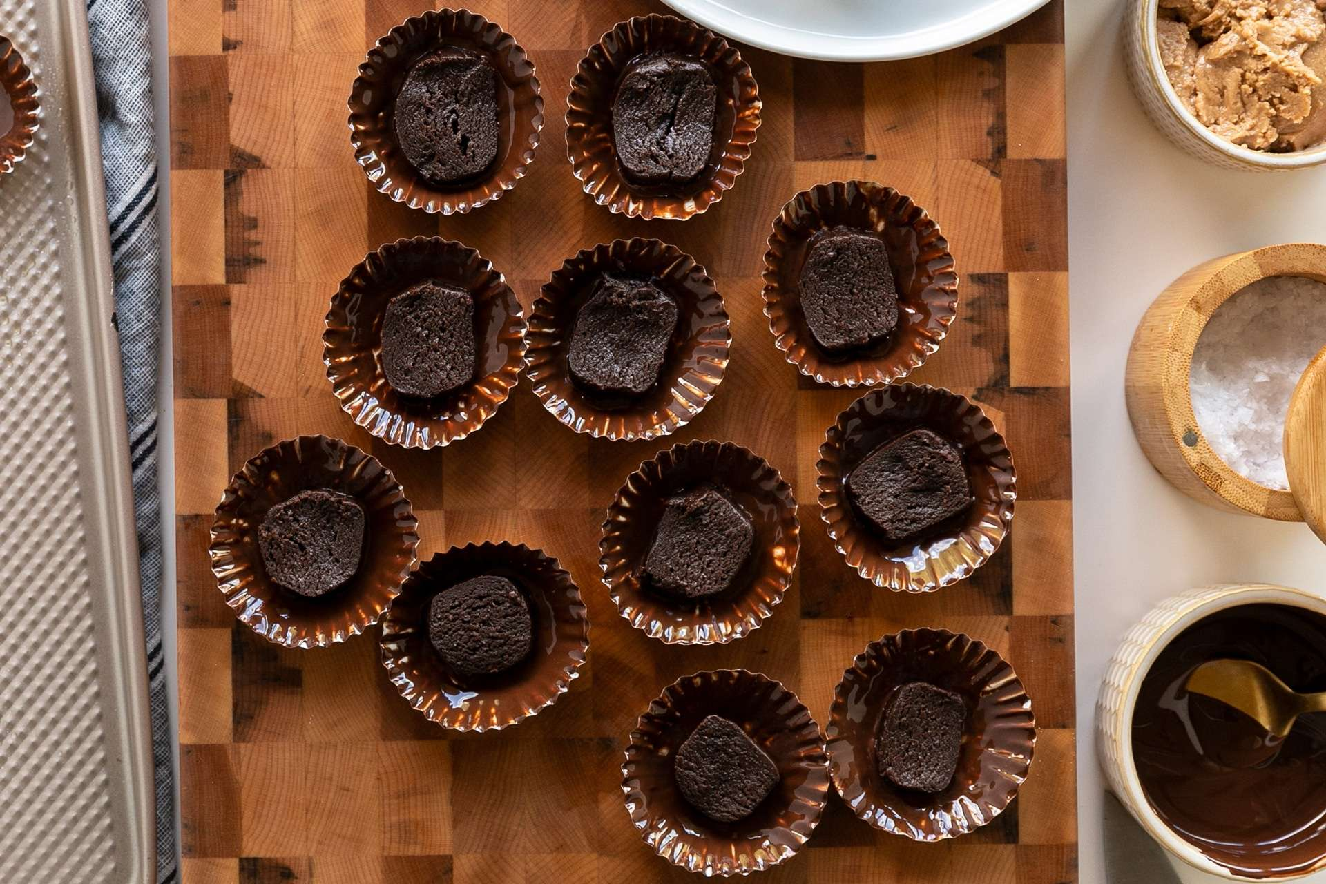 11 cupcake liners coated in dark chocolate then layered with fudgy brownie. Sitting on a maple end grain cutting board with corrugated baking sheet on the left side and peanut butter, sea salt flakes, and melted dark chocolate on the left.