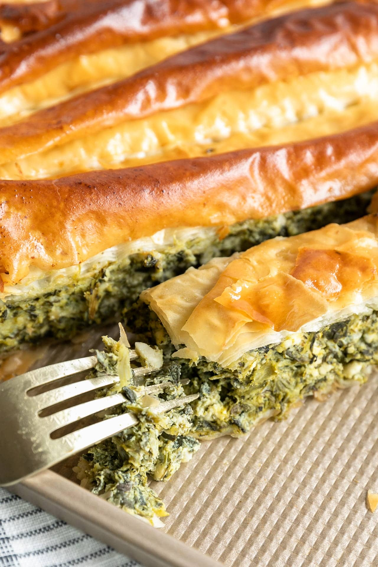 Spanakopita (Greek Spinach and Feta Pie) fresh out of the oven and sliced on an angle on a gold corrugated jelly roll baking sheet.