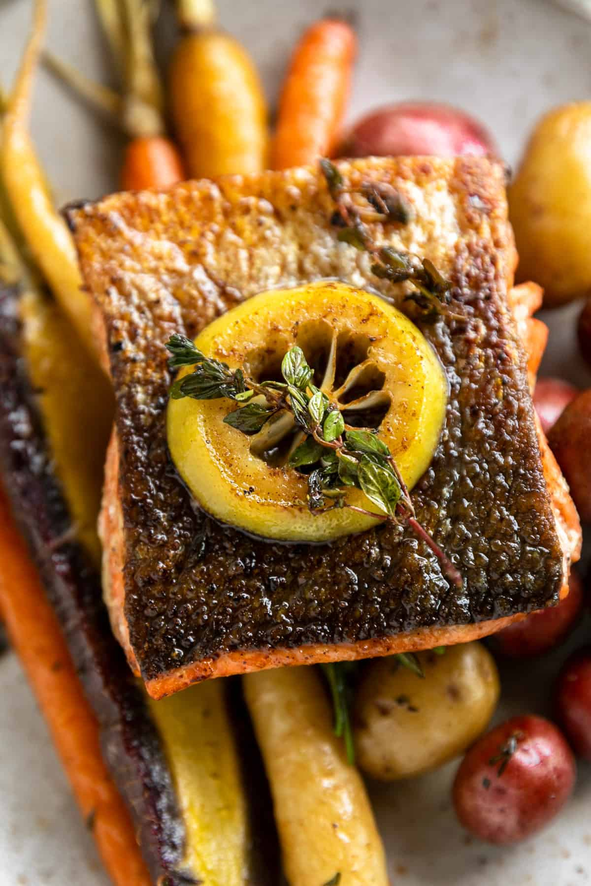 Brown Butter Herb Crispy Skin Salmon and vegetables. Crispy skin salmon is served on top of a bed of herbaceous roasted rainbow carrots and potatoes topped with a slice of lemon and thyme.
