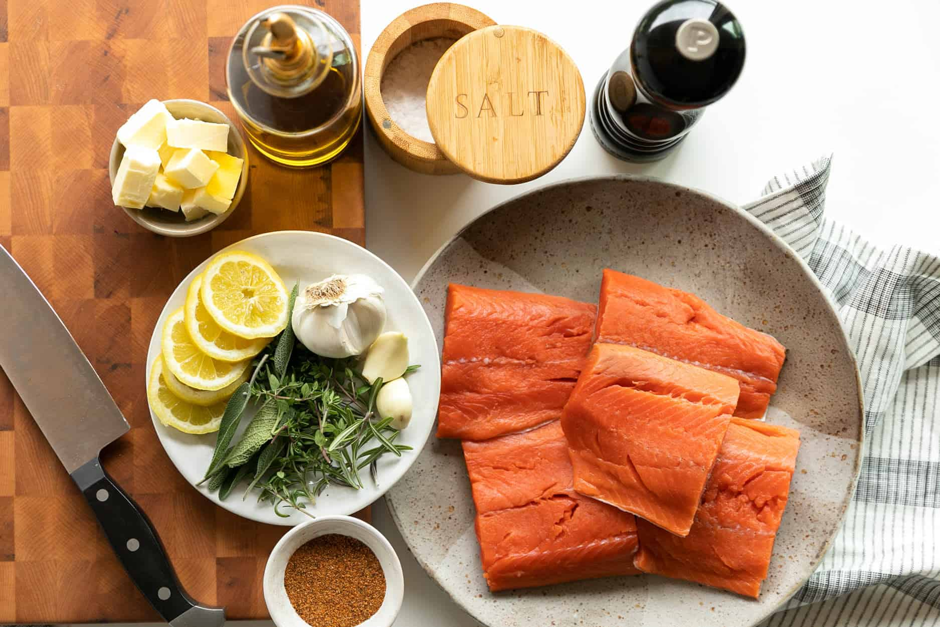 Ingredients to prepare Brown Butter Herb Crispy Skin Salmon and Vegetables. Cubed butter, sea salt flakes, olive oil, fresh ground pepper, lemon slices, garlic, rosemary, thyme, sage, Cajun seasoning and wild caught salmon.