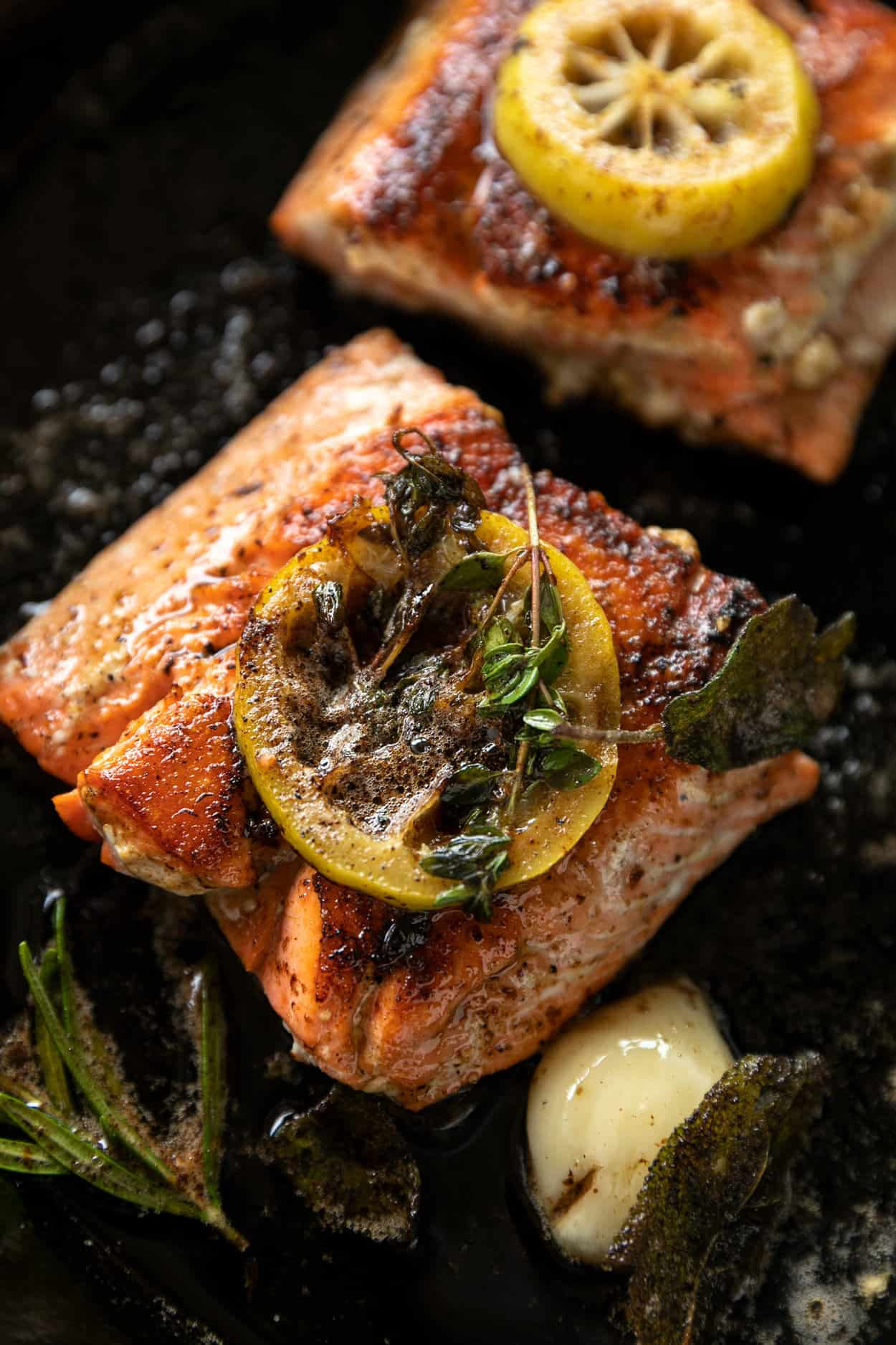 Cooking Brown Butter Herb Crispy Skin Salmon, skin side down in cast iron skillet with lemon slices and brown butter, rosemary, garlic, thyme and sage.