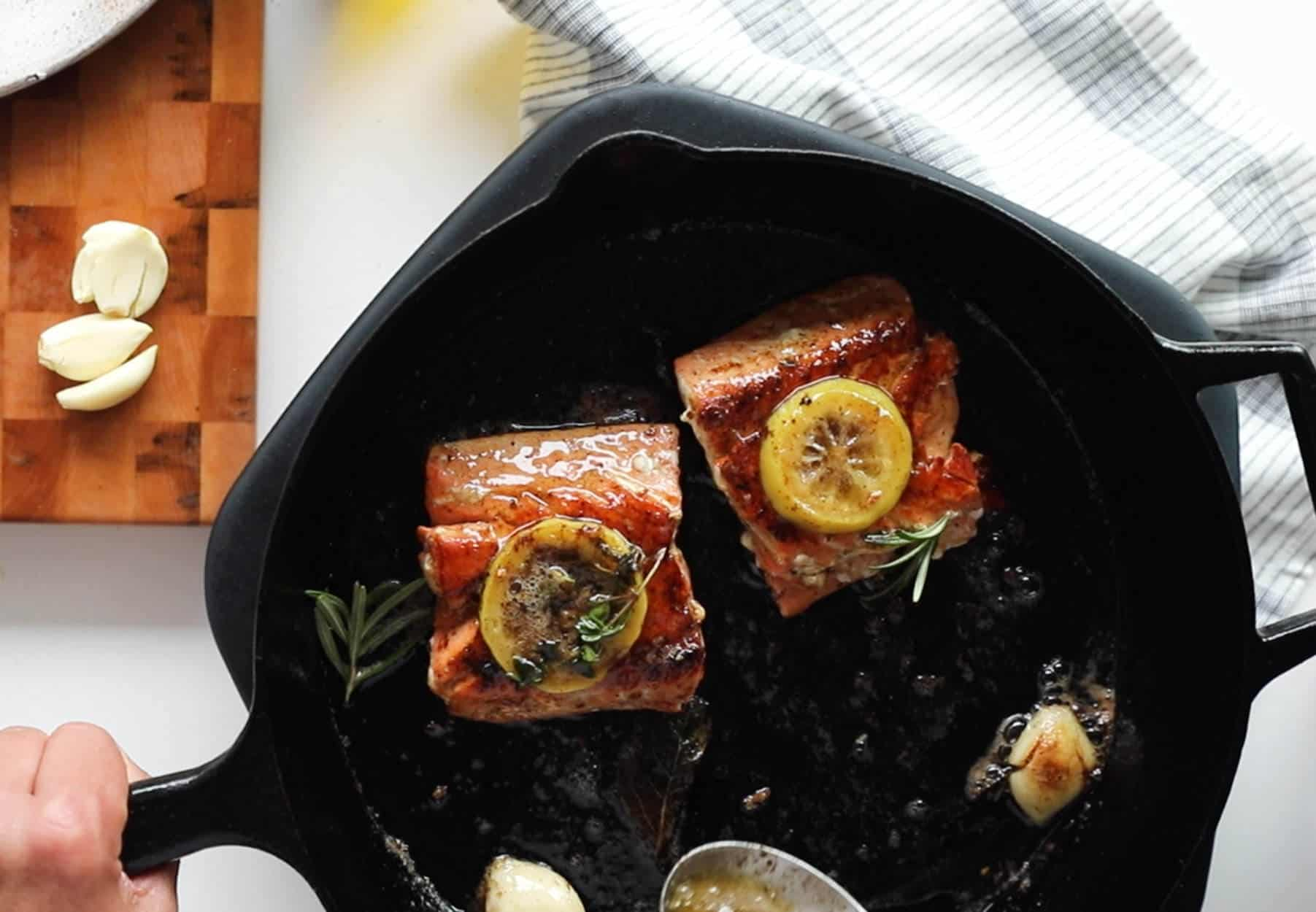 Sauteing and basting Brown Butter Herb Crispy Skin Salmon in cast iron pan with lemon slices and brown butter, rosemary, garlic, thyme and sage.