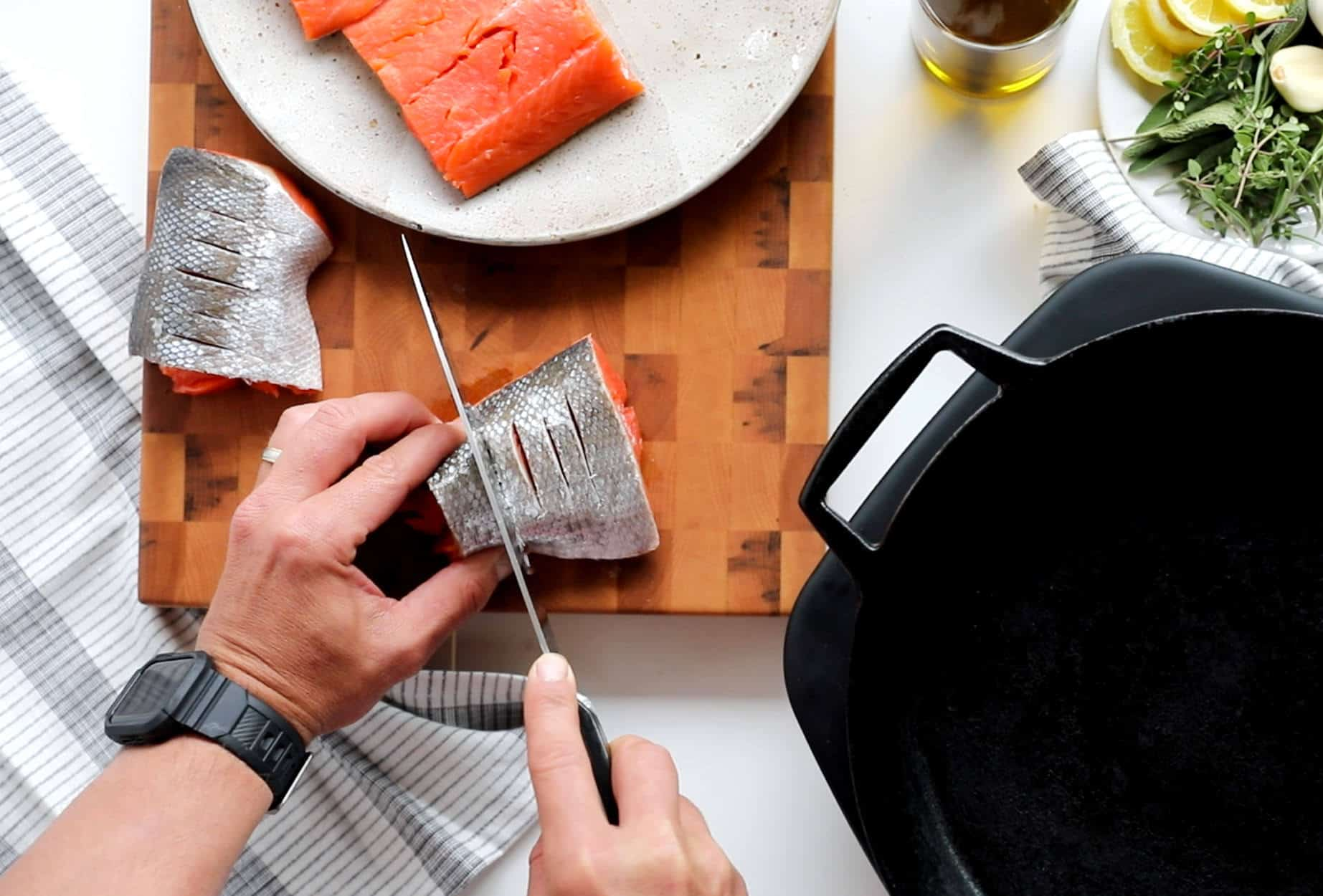 Brown Butter Herb Crispy Skin Salmon and Vegetables: Scoring salmon skin of a salmon filet with sharp knife prior to cooking.