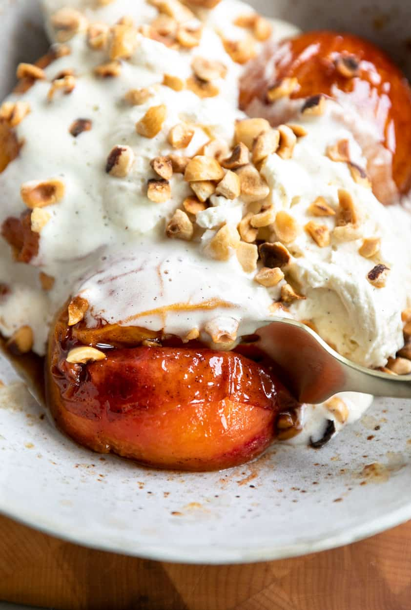 Vanilla Bourbon Peaches and Mascarpone Whipped Cream in extra large speckled bowl with chopped toasted hazelnuts on top and a gold fork slicing into a roasted peach.