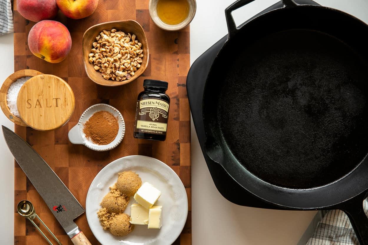 Ingredients to make Vanilla Bourbon Peaches and Mascarpone Whipped Cream: peaches, bourbon, hazelnuts, vanilla bean paste, cinnamon, nutmeg, butter, brown sugar, sea salt flakes and a cast iron skillet