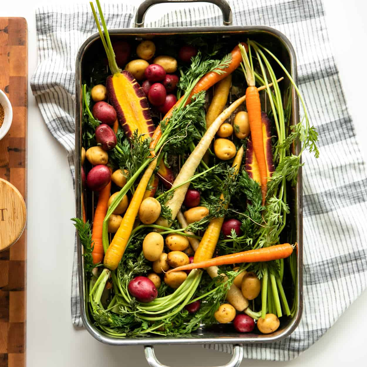 Brown Butter Herb Crispy Skin Salmon and Vegetables: Root Vegetables (rainbow carrots and potatoes) on a bed of herbs in a roasting pan.