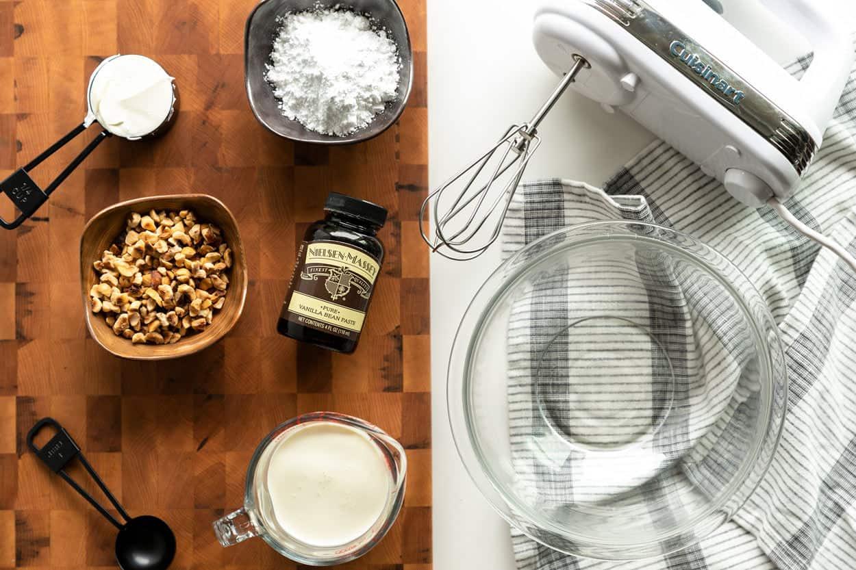 ingredients to make mascarpone whipped cream: powder sugar, heavy cream, and mascarpone and cuisinart hand mixer