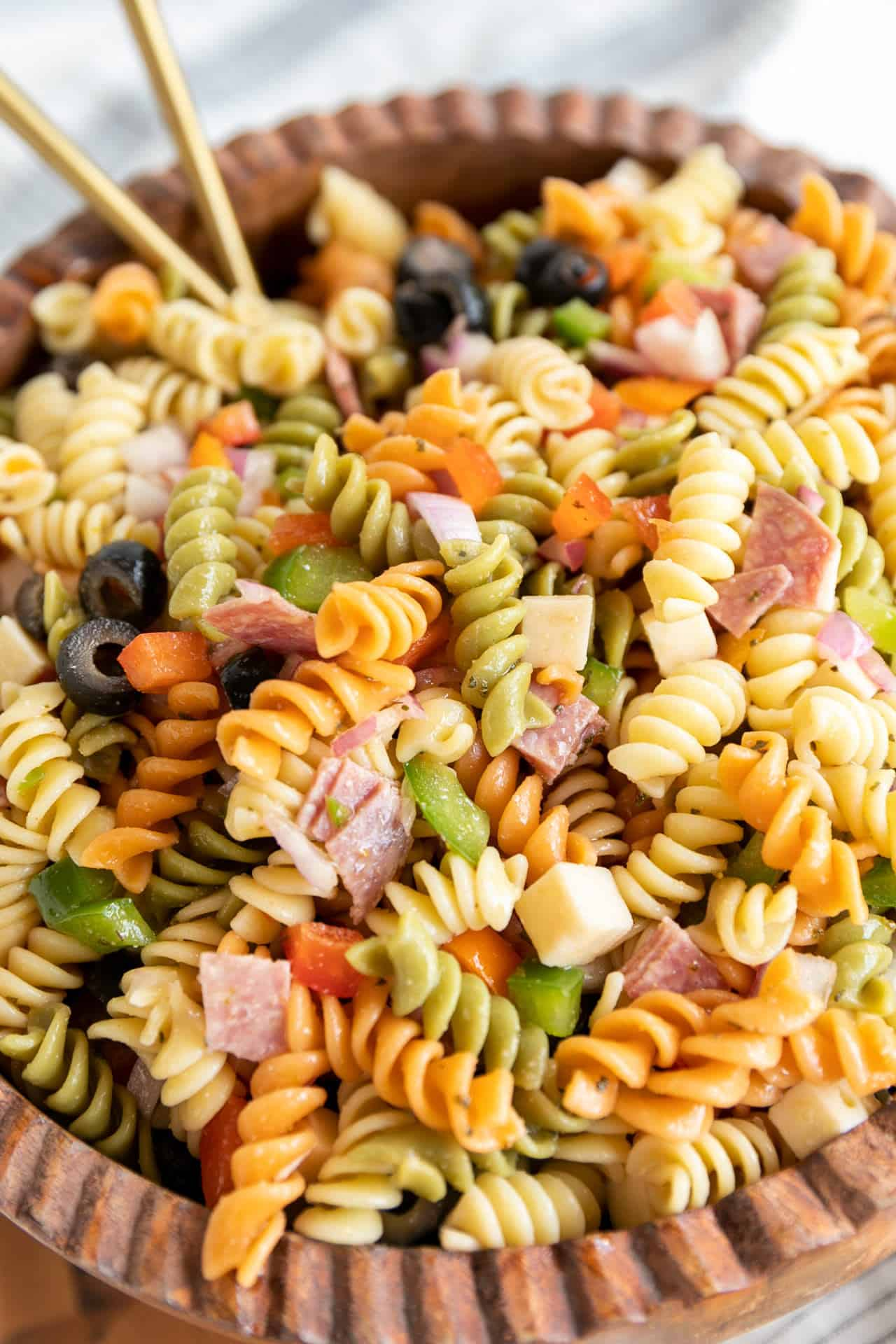 up close ready to serve Antipasto Pasta Salad up close with gold serving spoons in a wood bowl