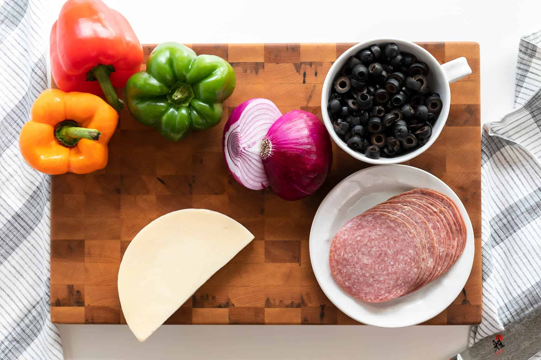 ingredients: red pepper, orange bell pepper, green bell pepper, provolone cheese block, salami, red onion, sliced black olives