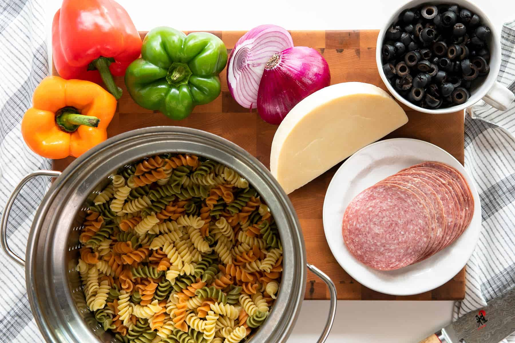 Pasta Salad ingredients: red pepper, orange bell pepper, green bell pepper, provolone cheese block, salami, red onion, sliced black olives and tri-color rotini pasta