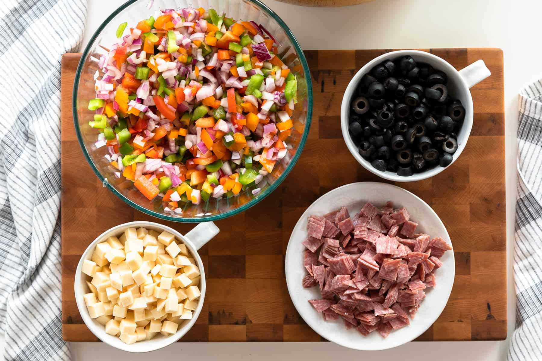 antipasto pasta salad prepped ingredients on a cutting board. diced bell peppers and red onion, sliced black olives, cubed provolone cheese, and salami cut in cubes