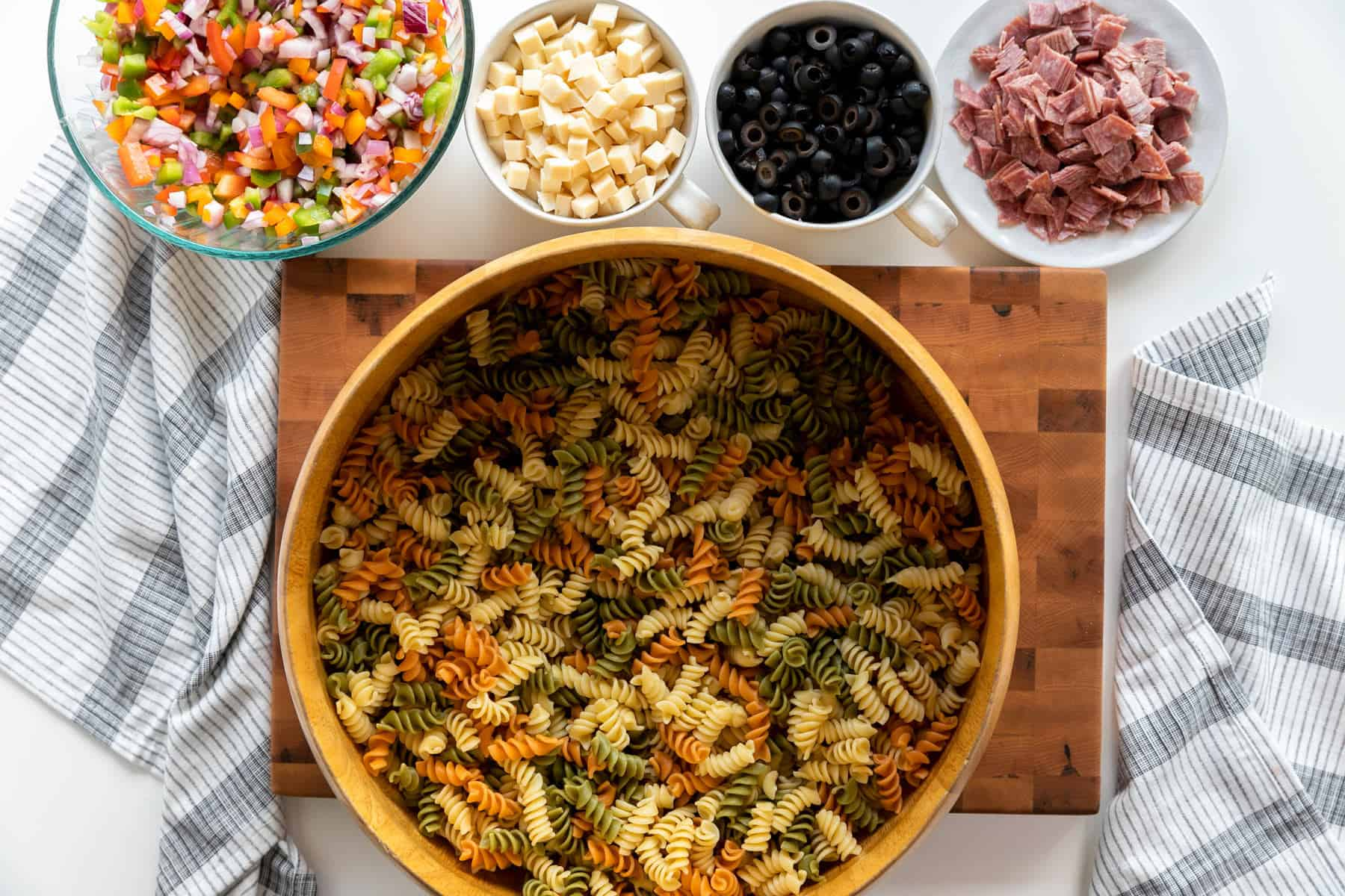 Overhead shot of Antipasto Pasta Salad with prepped ingredients on a cutting board. diced bell peppers and red onion, sliced black olives, cubed provolone cheese, and salami cut in cubes with big wooden bowl of tri-color rotini pasta