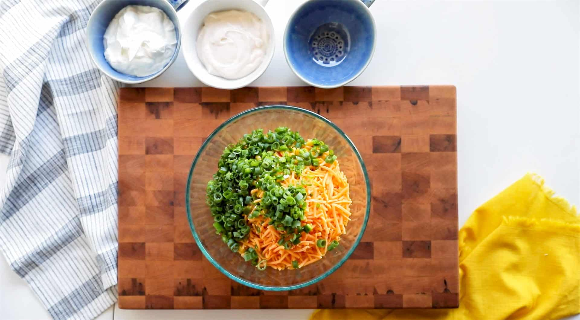 creamy fiesta corn dip ingredients: sour cream, mayonnaise, cheddar, green onion and jalapeño with fiesta corn. Mixing bowl on cutting board with cheddar and fiesta corn jalapeno, green onion