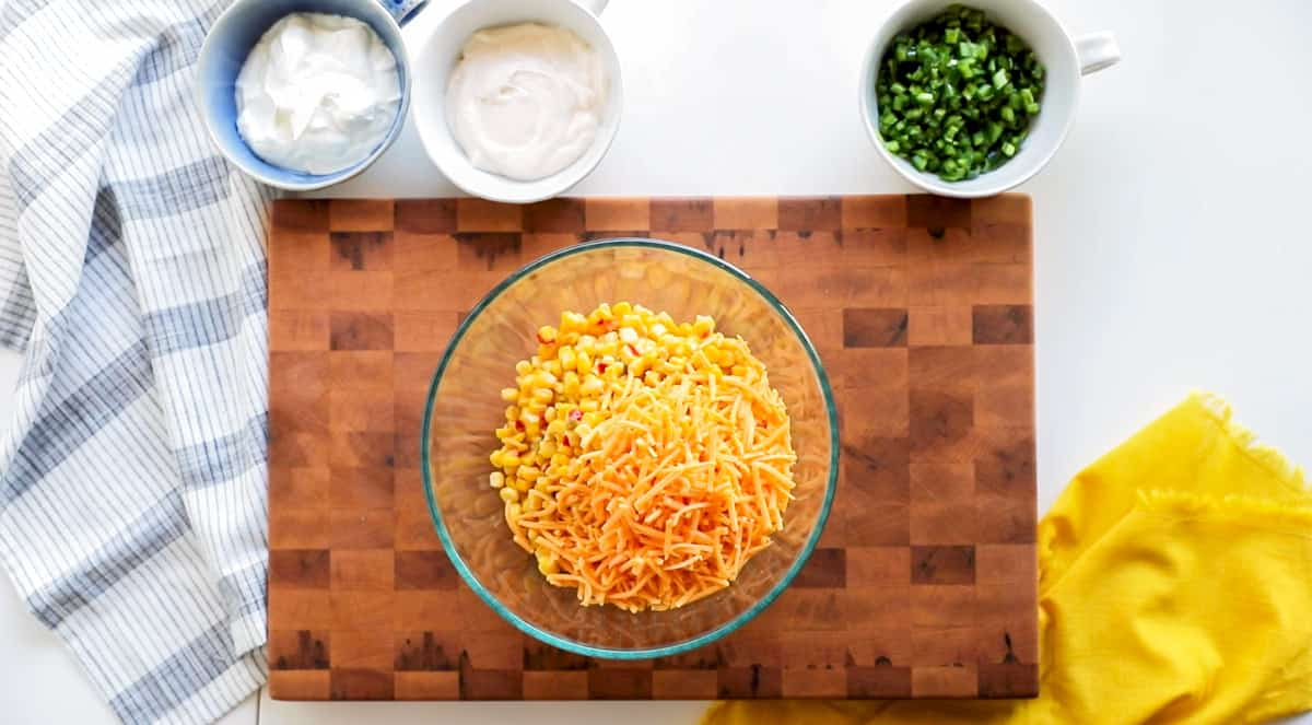 creamy fiesta corn dip ingredients: sour cream, mayonnaise, cheddar, green onion and jalapeño with fiesta corn. Mixing bowl on cutting board with cheddar and fiesta corn mixed.