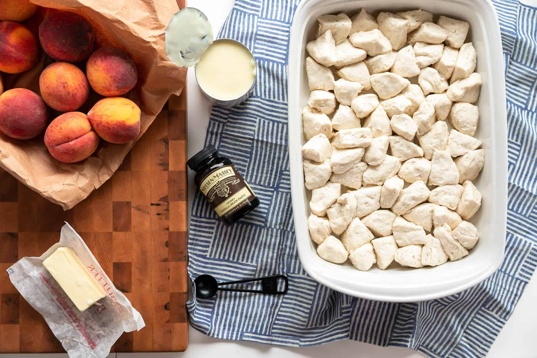 overhead picture of ingredients: whole peaches, sweetened condensed milk, vanilla bean paste, buttermilk biscuits in a while casserole dish and butter butter
