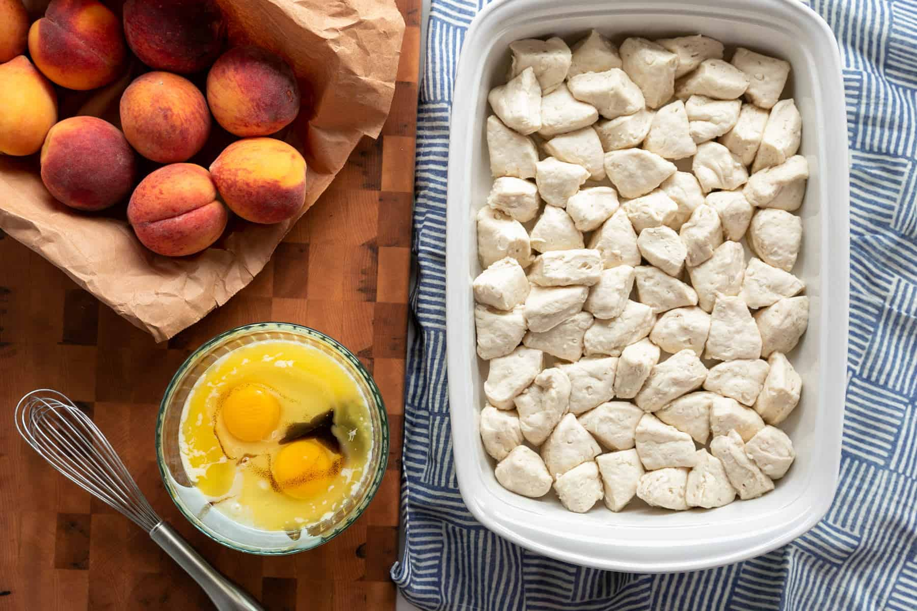 quatered buttermilk biscuits in a casserole dish. Whole peaches in a brown paper bag and a mixing bowl with sweetened condensed milk, egg and vanilla ready to mix and pour over the biscuits