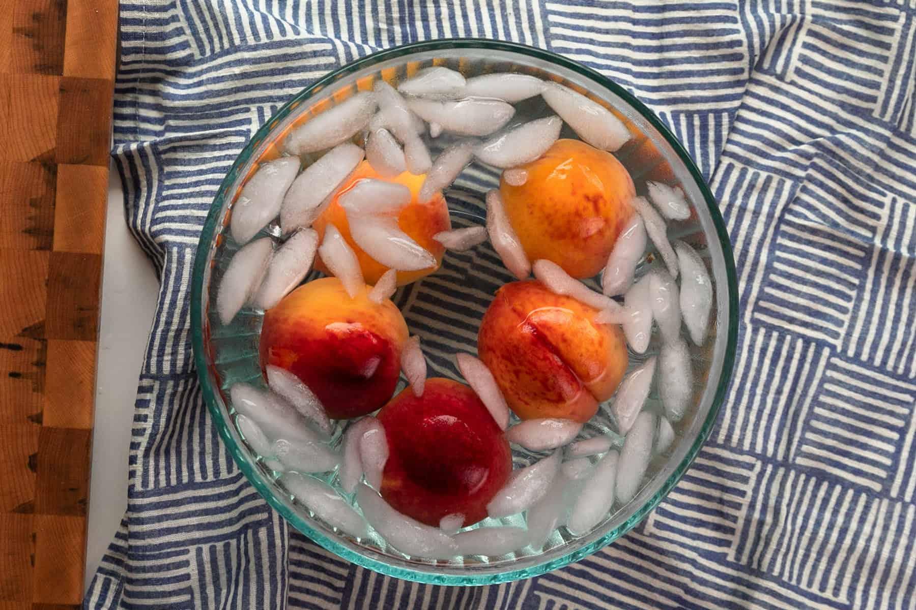 whole peaches in an ice bath