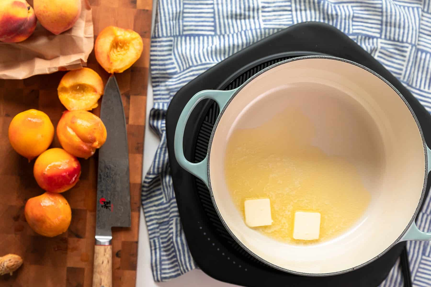 sliced peaches on an end grain maple cutting board with dutch oven melting butter preparing to saute the peaches