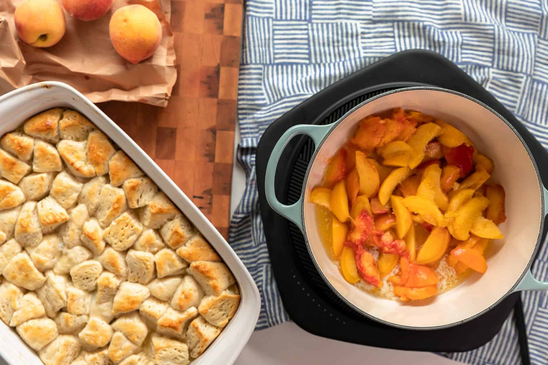 sliced peaches in a sea salt le creuset dutch oven with par baked buttermilk biscuits in casserole dish next to it