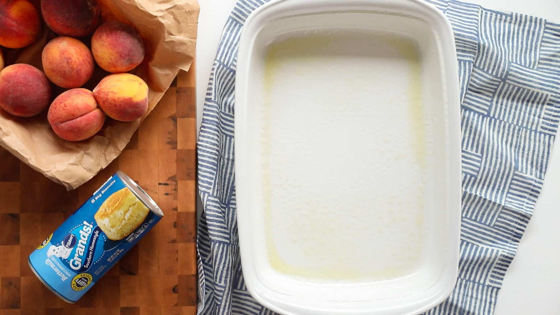 overhead picture of lightly coated casserole dish, pillsbury buttermilk biscuits and whole peaches in a brown bag