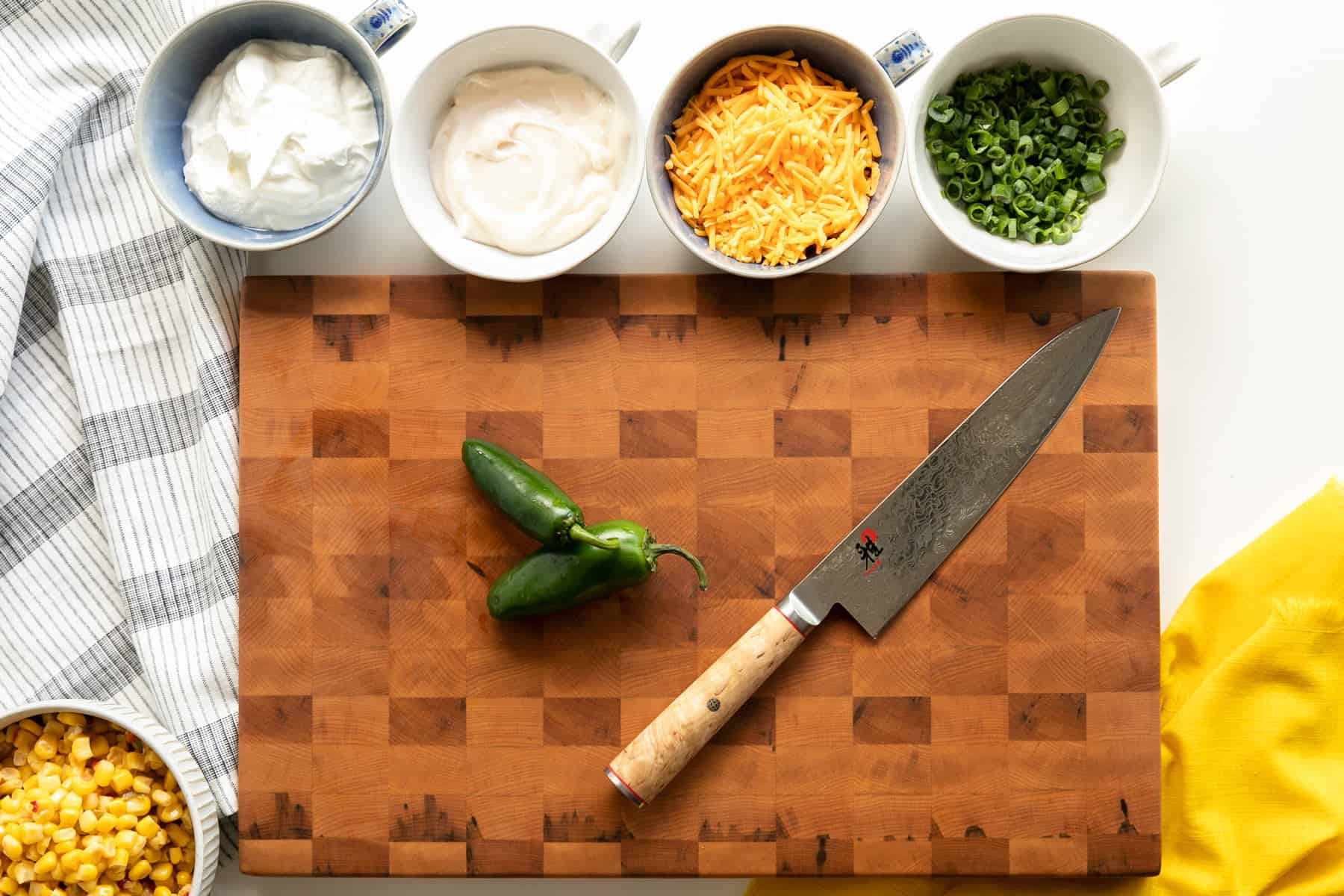 creamy fiesta corn dip ingredients: sour cream, mayonnaise, cheddar, green onion and jalapeño with fiesta corn. All portioned and ready to combine