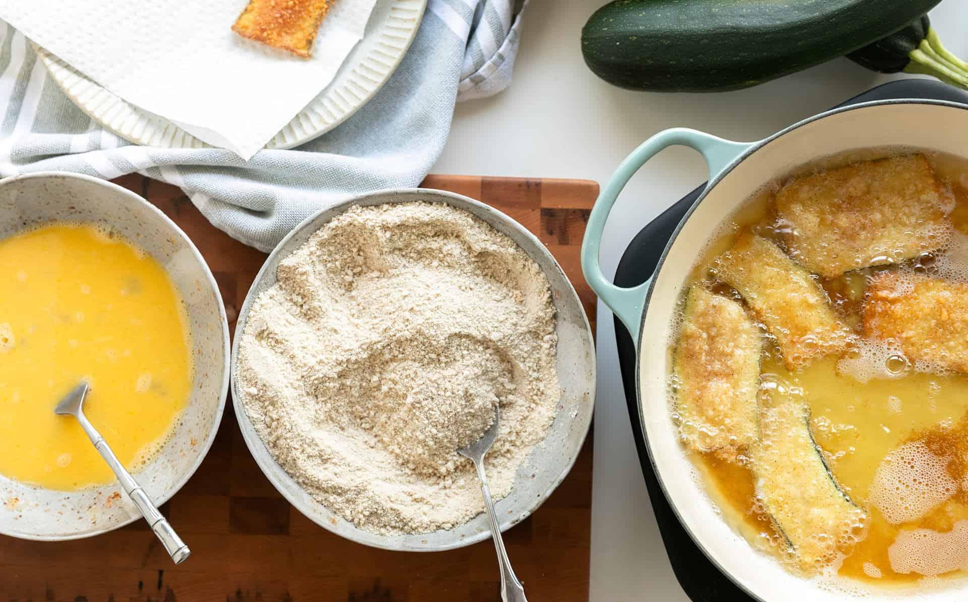 Overhead image of eggwash, breading and frying of Crispy Fried Zucchini with Marinara