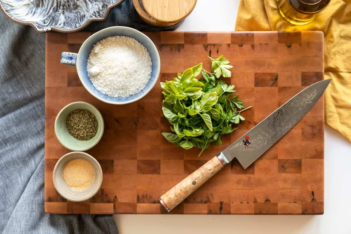 End grain cutting board with Kramer knife fresh herbs (basil and parsley), grated parmesan, dried oregano, granulated garlic to make Garlic Parmesan Monkey bread.