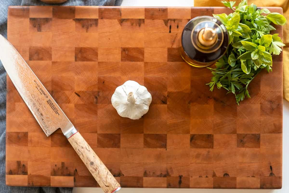 How to oven roast garlic. Overhead shot of end grain cutting board with a head of garlic, a knife, olive oil, and herbs on it.
